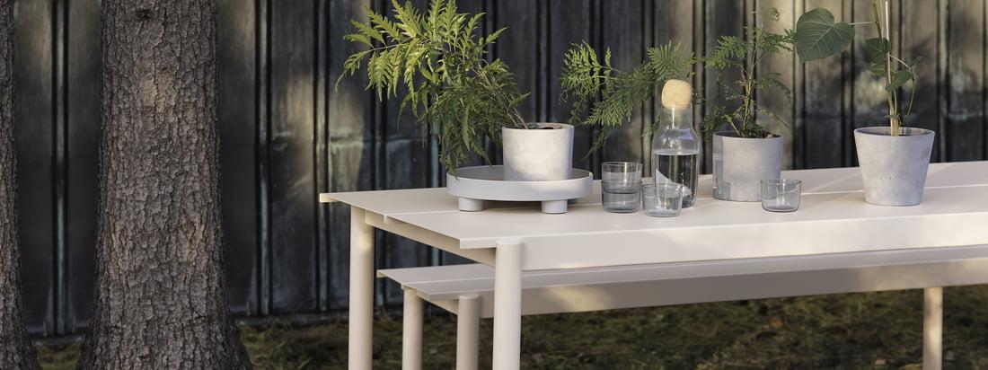 Linear Steel Bank und Tisch in weiß von Muuto in der Ambienteansicht. Tisch und Bank können aufgrund ihrer Fertigung aus Stahl perfekt im Garten genutzt werden und begeistern mit ihrem modernen Design.