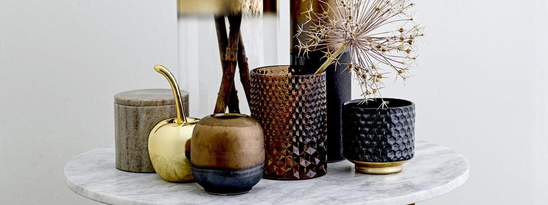 Der Teelichthalter aus Glas, die Glas-Vase mit einer Höhe von 35 cm die Deko-Kirsche und die Aufbewahrungsdose Marmor von Bloomingville machen sich toll auf einem runden Beistelltisch.