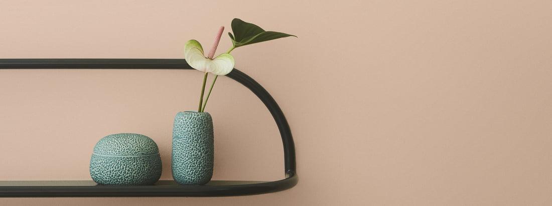 Gemma Aufbewahrungsdose mit Deckel von AYTM in der Ambiente-Ansicht. Die Aufbewahrungsdose und die Vase in der Farbe dusty green lassen sich gut auf einem Wandregal präsentieren.