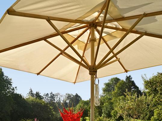 Der hochwertige Sonnenschirm von Skagerak ist in mehreren Größen, Formen und Materialien erhältlich. Unter den weißen Segeln des Schirms findet man an heißen Sommertagen Schutz vor der Sonne.