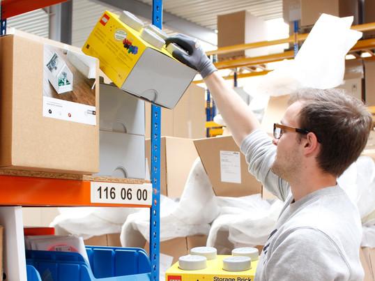 Fabian ordnet dem Storage Brick von Lego einem Regal im Connox- Lager zu.