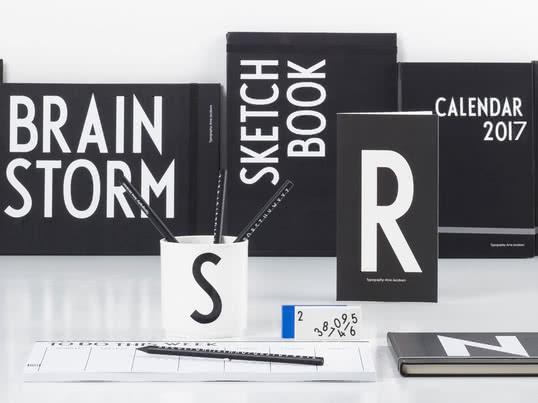 Design Letters bietet vom schwarz-weißen Notizbuch bis zum AJ Bleistift alle Utensilien für die Schule und das Büro. Arne-Jacobsen-Buchstaben verleihen Becher, Buch und Kalender eine persönliche Note.