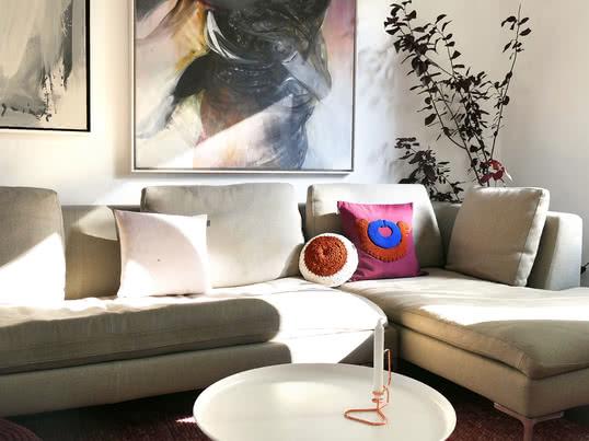 Das Nido Kissen Pichu von ames passt perfekt in die farbenfrohe Wohnzimmer Einrichtung. Der Lup Kerzenhalter von Hay in Kupfer komplementiert das warme Ambiente.