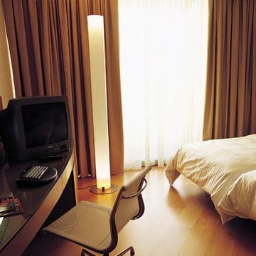Stylos Stehlleuchte von Flos in gemütlichem Schlafzimmer