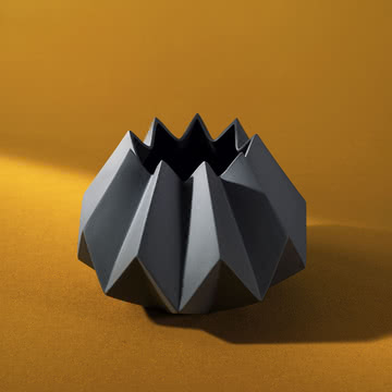 Schwarze Folded Vase auf orangenem Boden